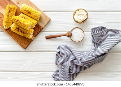 Grilled corn with salt and butter as farm food on white wooden background top view