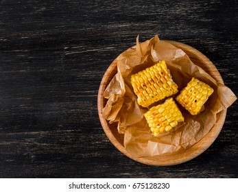 Grilled corn with salt on a black background viewed from above, flat top view.