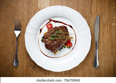 Grilled crusty shiny oily beef steak on a white plate with tomatoes and vegetables