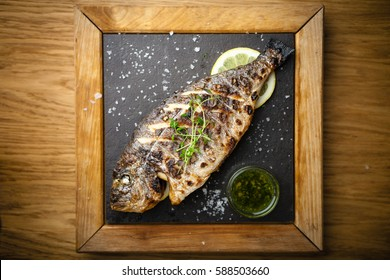 Grilled dorada fish with lemon and spinach served on a stone board