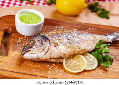 Grilled dorado fish with lemon and sauce on wooden board. Close up