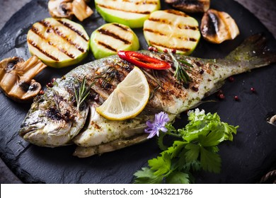 Grilled Dorado fish lemon slices, spices, herbs and vegetables on black stone. Mediterranean cuisine.
