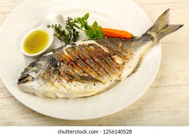 Grilled dorado fish with sauce, thyme and basil