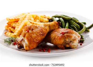 Grilled drumsticks with french fries and vegetables