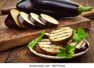 grilled eggplant and parsley leaves on wooden table