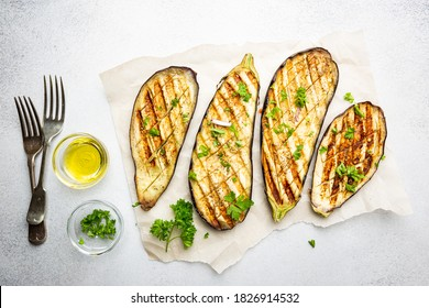 Grilled eggplant slices, garnished with fresh herbs, on white background, top view