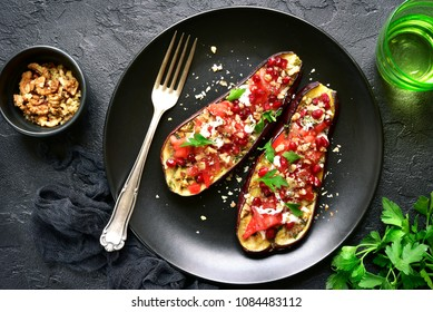 Grilled eggplant stuffed with tomatoes, nuts, pomegranate and yogurt dressing on a dark plate over black slate, stone or concrete background.Top view.