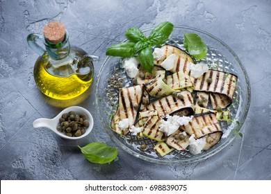 Grilled eggplant and zucchini with olive oil, capers and cheese, gray stone background, studio shot