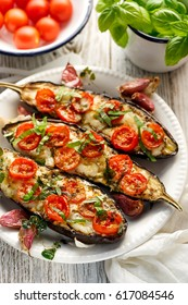 Grilled eggplants with cheese, cherry tomatoes and basil on white plate
