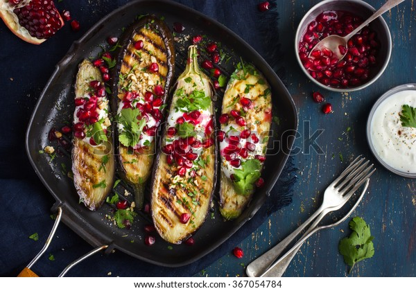 grilled eggplants with garlic yogurt sauce, walnuts and pomegranate, top view