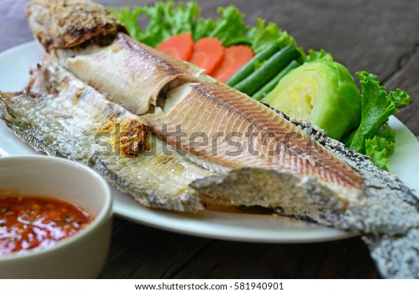 Grilled fillet fish on white plate, serv with fresh vegetables and spicy sauce on the wooden table. (Thai Foods)