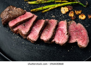 Grilled fillet mignon beef steak set, with onion and asparagus, on plate