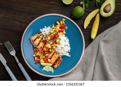 Grilled fillet of salmon with rice garnish and exotic fruit sauce made of mango, avocado, pepper and onion on a rustic table. Top view shot above.