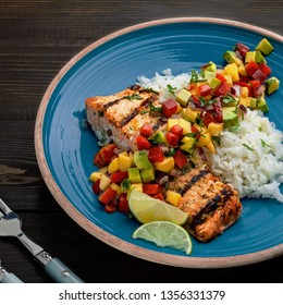 Grilled fillet of salmon with rice garnish and exotic fruit sauce made of mango, avocado, pepper and onion on a rustic wooden table.