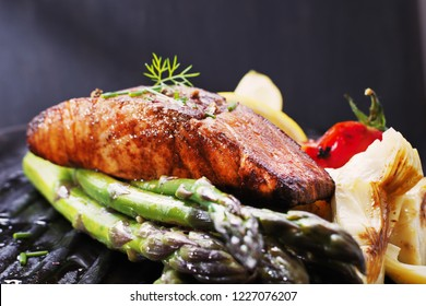 Grilled fillet of salmon with warm salad with asparagus and lemon on a black background. top view, selective focus, close up.
