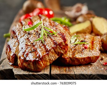 Grilled fillet steaks on wooden cutting board