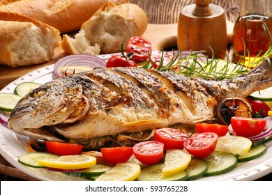 Grilled fish with baguette and vegetables on white plate