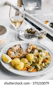 Grilled fish with boiled vegetables and a glass of white wine served in Estoril, Portugal.