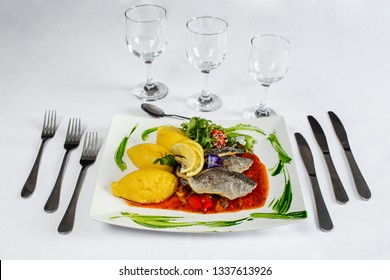 grilled fish with fish brine and hominy on plate and mise en place