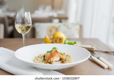 Grilled fish fillet with couscous and sauce on the white plate with white wine