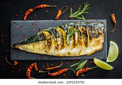Grilled fish fillets with lime on black slate board, scomber with vegetables and herbs