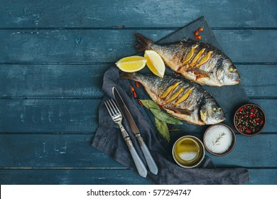 Grilled fish with herbs and lemon on wooden background, top view. Mediterranean luxurious seafood concept