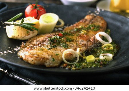 Grilled fish with lemon and rosemary in the sauce