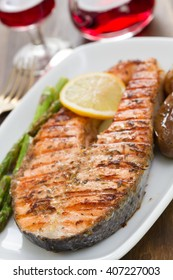 grilled fish with lemon and vegetables on white dish