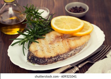 grilled fish with lemon in white dish on wooden background