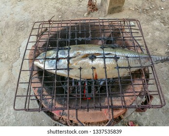 Grilled fish on a charcoal stove