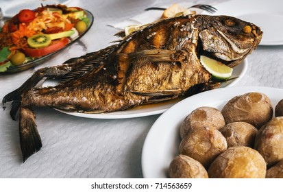 Grilled fish on plate, canarian wrinkly potatoes and salad with vegetables and fruits. Tenerife, Canary islands