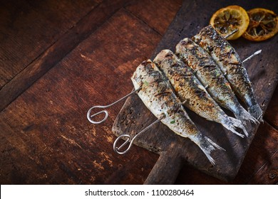 Grilled fish on skewers served on rustic wooden table viewed in close-up from above with copy space