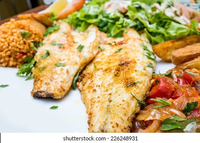 grilled fish and rice with many  vegetables and french fries