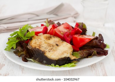 grilled fish with salad on the white plate