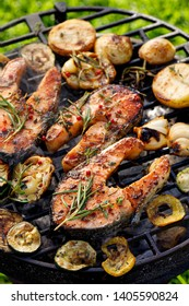 Grilled fish, grilled salmon steak with the addition of rosemary, aromatic spices and vegetables on the grill plate outdoors, top view, close-up. Grilled seafood