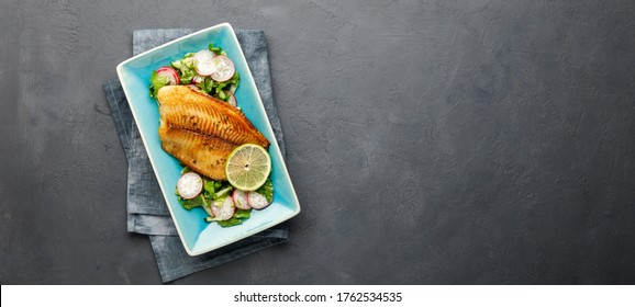 Grilled fish sea bass fillet with green lettuce and radish. Black stone background. Top view with copy space.