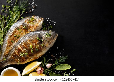 Grilled fish, sea bream with additions, herbs, olive oil, spices on a black background. Composition in the bottom left corner. Healthy eating concept