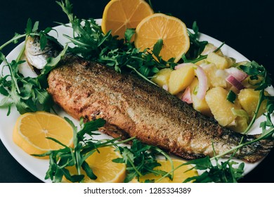 Grilled fish served on plate with potato, arugula and lemon
