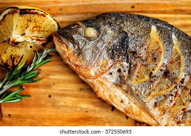 Grilled Fish with Slices of Lemon on Wooden Board