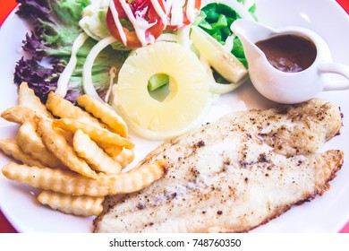 Grilled fish steak salad on back color background ready to eat
