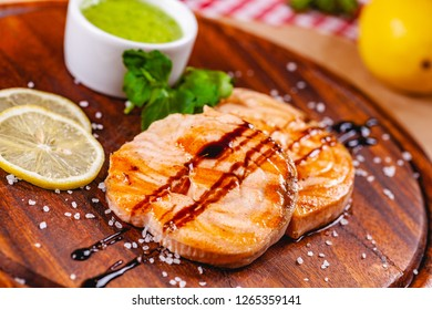 Grilled fish steak served with sauce and lemon on wooden cutting board. Close up
