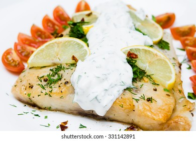 grilled fish with vegetables and cream sauce on white plate