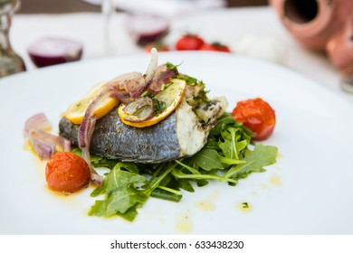 grilled fish with vegetables on white elegant plate