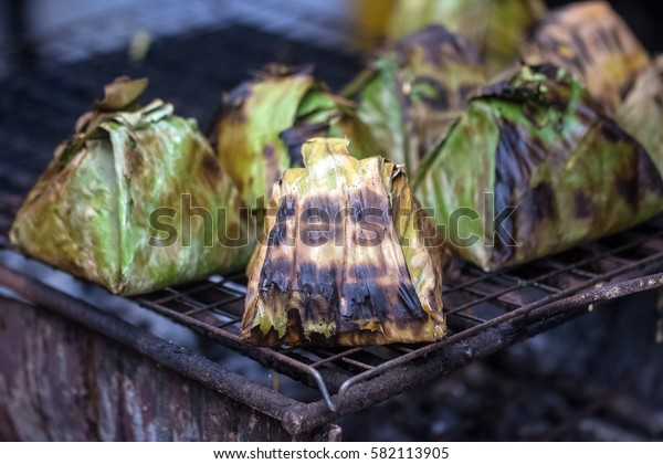 Grilled  fish wrap with banana leaves on grille