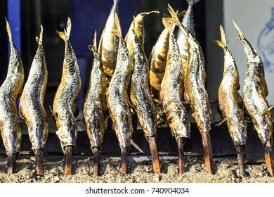 Grilled fishes on fire at a folk festival. Typical bavarian fish on on sticks.