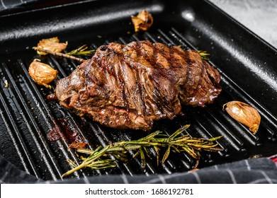 Grilled Flat Iron steak on a grill pan, marbled beef. Gray background. Top view