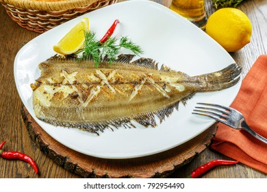 Grilled flounder on white plate garnished with lemon and dill
