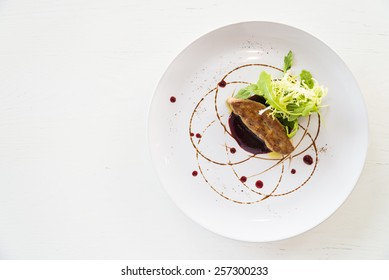 Grilled foie gras with sweet sauce in white dish - selective focus point