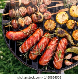 Grilled food, assorted of grilled products, grilled sausages, skewers and vegetables on a bbq grill plate, outdoor, close-up.