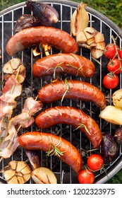 Grilled food. Grilled pork sausages, bacon and vegetables on the grill plate, top view, outdoor. Barbecue, bbq
